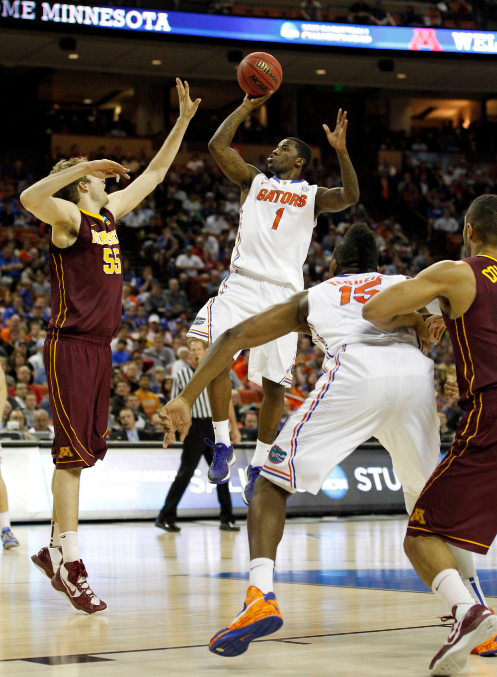 . University of Florida guard Kenny Boynton (C) shoots over University of Minnesota center Elliott Eliason (L) as forward Will Yeguete blocks out during the first half of their third round NCAA basketball game in Austin, Texas March 24, 2013.   REUTERS/Mike Stone