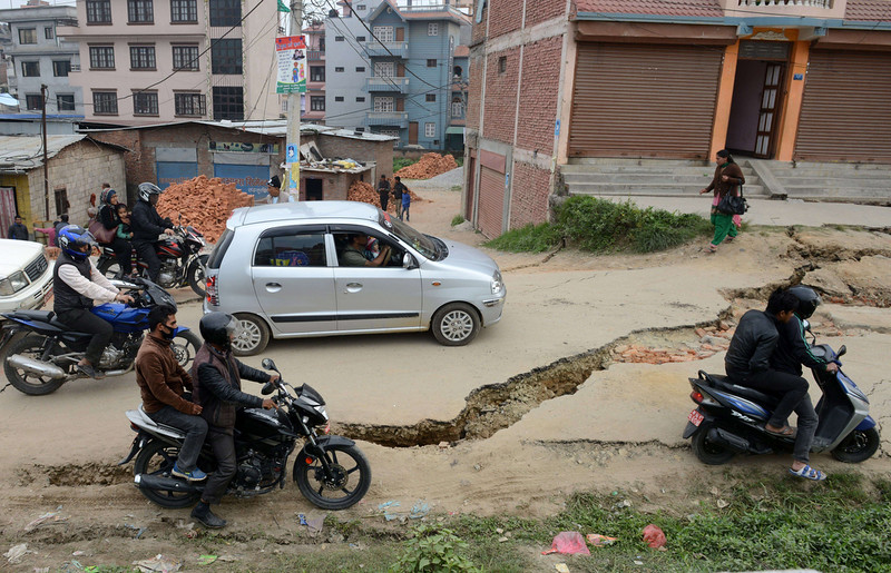 . Nepalese residents drive past road damage following an earthquake in Kathmandu on April 26, 2015. International aid groups and governments intensified efforts to get rescuers and supplies into earthquake-hit Nepal on April 26, 2015, but severed communications and landslides in the Himalayan nation posed formidable challenges to the relief effort. As the death toll surpassed 2,000, the US together with several European and Asian nations sent emergency crews to reinforce those scrambling to find survivors in the devastated capital Kathmandu and in rural areas cut off by blocked roads and patchy phone networks. PRAKASH MATHEMA/AFP/Getty Images