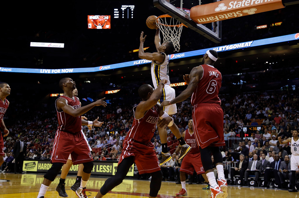 . Utah Jazz\'s Alec Burks (10) goes up to shoot as Miami Heat\'s Chris Bosh, left, Dwyane Wade, center, and LeBron James (6) look on in the first half of an NBA basketball game, Monday, Dec. 16, 2013, in Miami. (AP Photo/Lynne Sladky)
