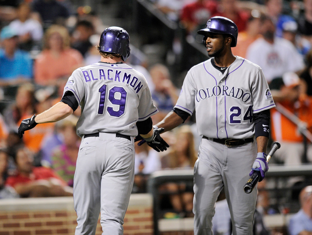 . Colorado Rockies\' Charlie Blackmon (19) celebrates his home run with Dexter Fowler (24) against the Baltimore Orioles during the eighth inning of a baseball game, Friday, Aug. 16, 2013, in Baltimore. The Rockies won 6-3. (AP Photo/Nick Wass)