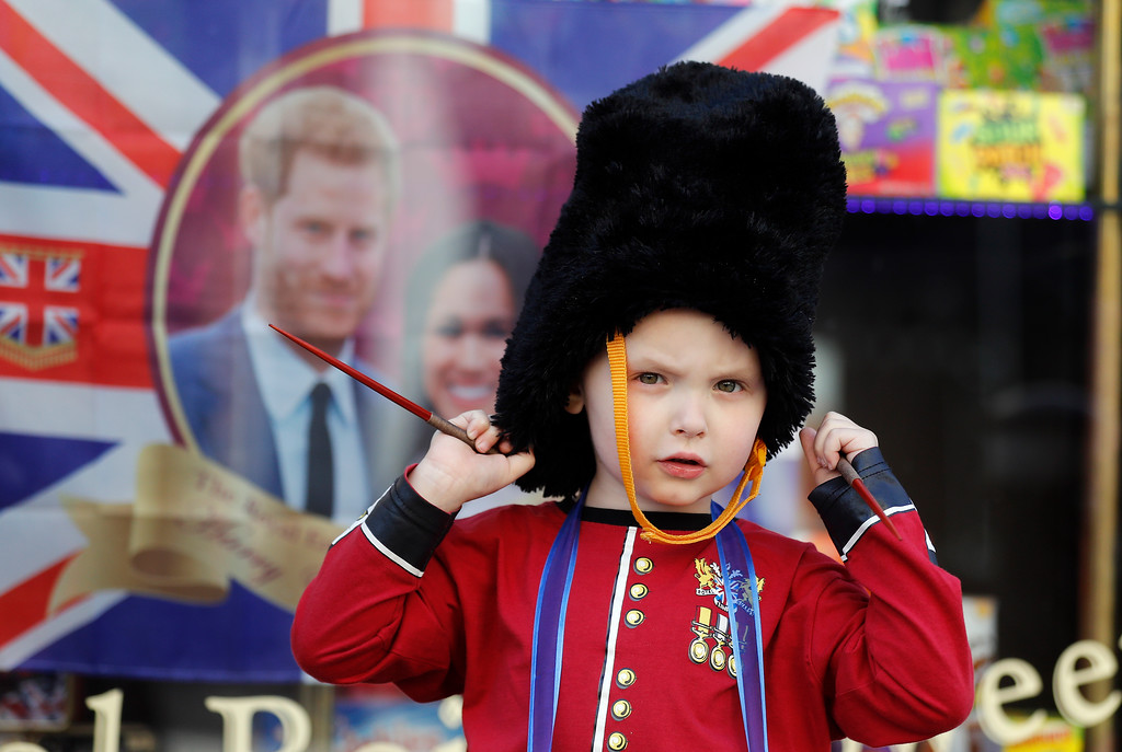 . 4 years old boy George is dressed as a soldier as he walks past a decorated shop window in Windsor, Tuesday, May 15, 2018. Preparations are being made in the town ahead of the wedding of Britain\'s Prince Harry and Meghan Markle that will take place in Windsor on Saturday May 19.(AP Photo/Frank Augstein)