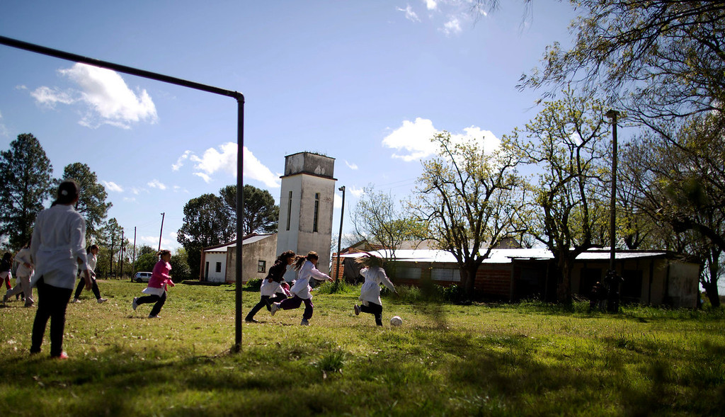 . Students play soccer during recess at a rural school near Concepcion del Uruguay, Entre Rios province, Argentina on Sept. 24, 2013. Teachers say the farm that abuts their school yard has been illegally sprayed with pesticides, even during class time. In Entre Rios, teachers reported that sprayers failed to respect legally required 50 meter setbacks outside 18 schools, and doused 11 of them while students were in session. Five teachers have since filed police complaints. (AP Photo/Natacha Pisarenko)