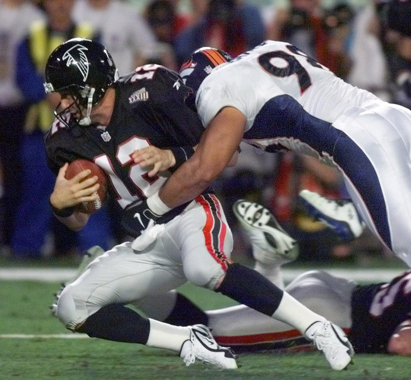 . Atlanta Falcons quaterback Chris Chandler is wrapped up by Denver Broncos defense end Maa Tanuvasa during the second quarter of Super Bowl XXXIII at Pro Player Stadium in Miami, Sunday, Jan. 31, 1999. The Broncos defeated the Falcons 34-19. (AP Photo/Doug Mills)