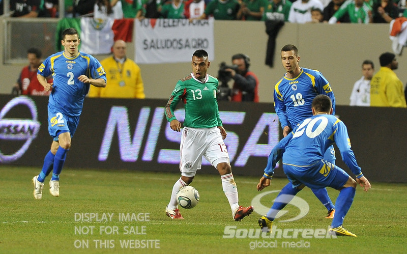Mexico's Forward Edgar Pacheco (#13) looks shocked that he's surrounded by many defenders as Bosnia-Herzegovina's Defender Mensur Mujdza (#2) gives chase and Bosnia-Herzegovina's Midfielder Zvjezdan Misimovic (#10) closes in during Soccer action between Bosnia-Herzegovina and Mexico.  Mexico defeated Bosnia-Herzegovina 2-0 in the game at the Georgia Dome in Atlanta, GA.