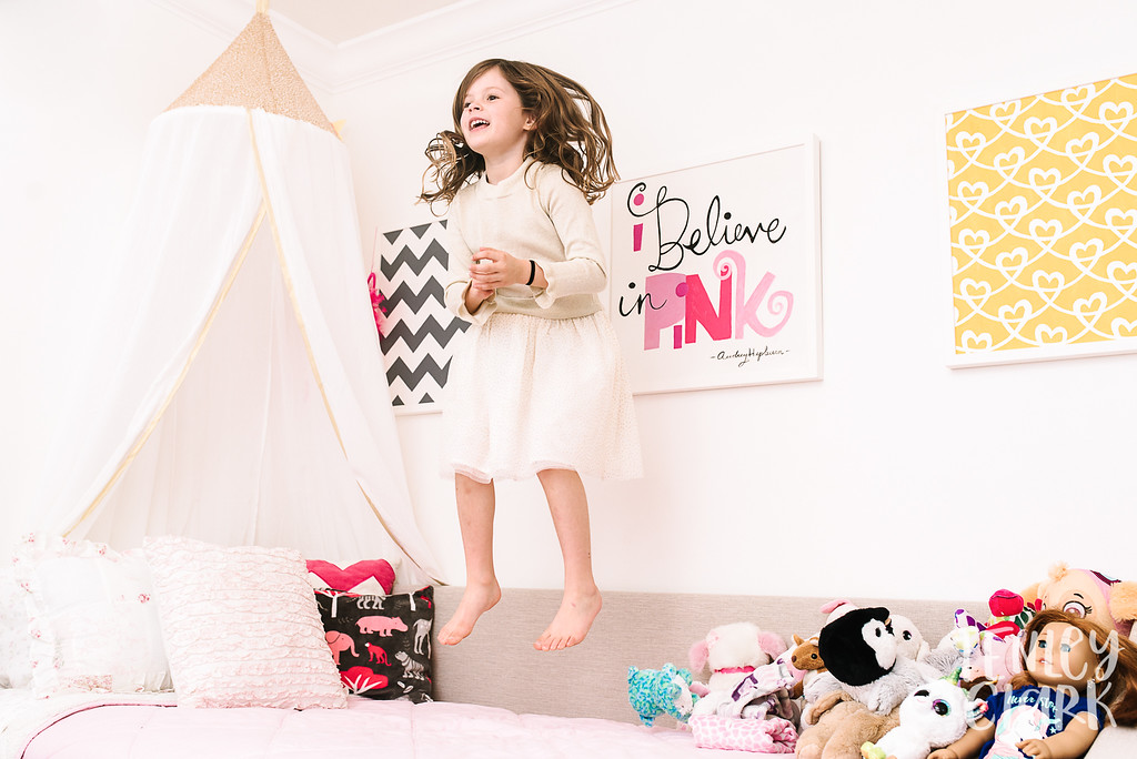 Little girl jumping on bed in pink girly room.Lifestyle in-home family photoshoot in Marin, CA by Tenley Clark Photography.