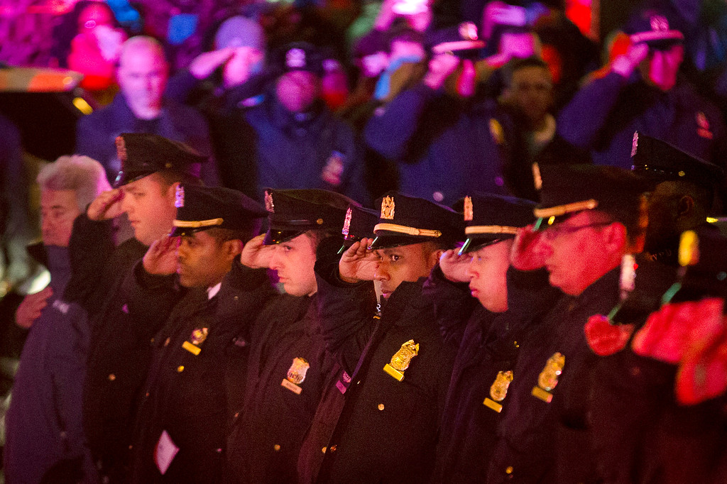 . Mourners stand at attention as the bodies of two fallen NYPD police officers are transported from Woodhull Medical Center, Saturday, Dec. 20, 2014, in New York. An armed man walked up to two New York Police Department officers sitting inside a patrol car and opened fire Saturday afternoon, killing one and critically wounding a second before running into a nearby subway station and committing suicide, police said. (AP Photo/John Minchillo)