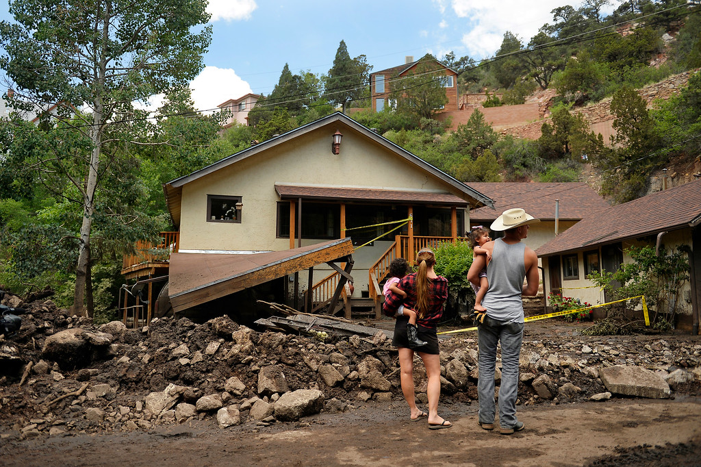. Manitou Springs, CO. - July 02: Kim Moses, her children and a neighbor look at the damage to her mothers house when a flash flood washed through houses, streets and businesses after a downpour over the Waldo Canyon burn scar in El Paso County July 02, 2013 Manitou Springs, Colorado. (Photo By Joe Amon/The Denver Post)