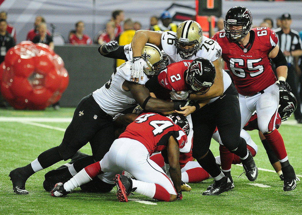 . Matt Ryan #2 of the Atlanta Falcons is sacked by Keyunta Dawson #55 and Akiem Hicks #76 of the New Orleans Saints at the Georgia Dome on November 21, 2013 in Atlanta, Georgia. (Photo by Scott Cunningham/Getty Images)