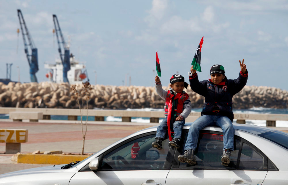 . Libyan children wave national flags near the seaport during a rally in Benghazi, Libya, Friday, Feb, 15, 2013. Libyans are preparing to mark the second anniversary of the uprising that ousted Moammar Gadhafi. (AP Photo/Mohammad Hannon)