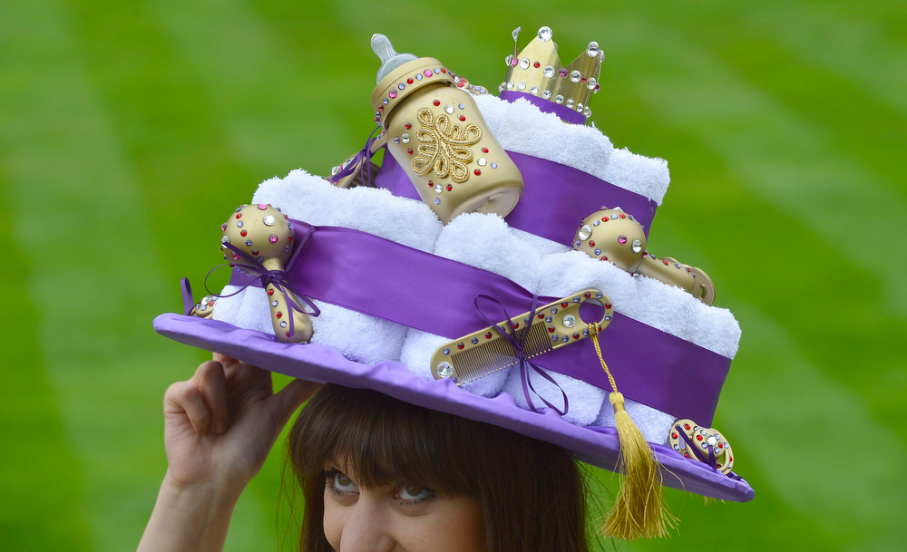 . A racegoer arrives for Ladies\' Day wearing a hat inspired by the forthcoming royal baby at the Royal Ascot horse racing festival at Ascot, southern England June 20, 2013.  REUTERS/Toby Melville