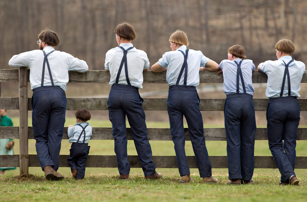 Description of . Amish boys watch a game of baseball outside the school house in Bergholz, Ohio on Tuesday, April 9, 2013.  Many Amish families gathered following the final day of school for a celebration and farewell picnic.  (AP Photo/Scott R. Galvin)