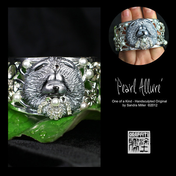 """PEARL ALLURE-CLICK HERE TO VIEW VIDEO DESCRIPTION IN A NEW WINDOW   Elegant silver, glass pearl and crystal hinged cuff bracelet   Ever since my 2011 Trunk Show I have received dozens of requests to repeat the elaborate cuff bracelet I made. I finally found a few of the same high end hinged cuffs and am pleased to offer 3 different designs at this 2012 Show  The foundation for the bracelet as I mentioned is a sturdy, slightly oval shaped hinged cuff which stays very securely closed with pressure from the spring hinge on one side. The finish is a highly polished silver tone open design with embedded crystals. The oval shape stays in place without flipping on the wrist much better than a round cuff.  To this exquisite blank """"canvas"""" I added a gorgeous chow headstudy (her name is """"Sparkle""""),  handsculpted and carved  in polymer clay.  The entire head was sculpted and detailed with the tip of a needle and knitting needles.  The pearlized silver was added in multiples layers to give a lot of depth and richness to the surface, then  once fired, I added a subtle black patina to the recesses to make the details really pop!! Multiple coats of waterproof sealer are added for extra protection.  Now comes the bling!! I purchased a drawer FULL of a tiara factory (1920's) bits and pieces back in the 90's and had a blast combing that Drawer O Glitz, to find the perfect Tiara parts for this perfect chow!!  Below her chin I applied crystals that are alive with icy glimmer and also put a single large Swarovski on her forehead like an Indian 'bindi""""….Sparkle loved  that part the best!!!  Half pearl cabochons were removed from one of the vintage Tiaras and applied to the entire front of the bracelet as well.  This is one of those designs that will stop traffic and goes with everything!!  Besides the obvious dressy look,  couldn't you just see this  with jeans, a black shirt and a pair of glitzy earrings….and stripy black sandals or sexy boots?  The sky is the limit   STRONG HINGED OVAL"""