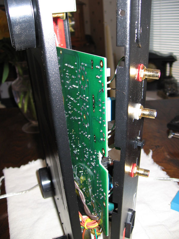 To access the underside of the circuit board, remove the screws holding it to the chassis, remove the two screws on the underside of the chassis holding the back panel in place, and gently pull the back panel away from the chassis. Now you can lift the board. Use solder wick to remove excess solder from the holes where the caps are soldered and, while holding the iron to a connection, gently lift that side of the cap. Then do the same to the other side until the cap is free of the board. Do the same with the other cap. No other connections need to be unsoldered to do this.
