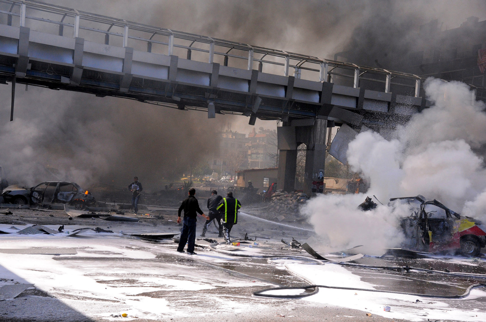 Description of . This photo released by the Syrian official news agency SANA, shows Syrian fire fighters extinguishing burning cars after huge explosion that shook central Damascus, Syria, Thursday, Feb. 21, 2013. A car bomb shook central Damascus on Thursday, exploding near the headquarters of the ruling Baath party and the Russian Embassy, eyewitnesses and opposition activists said. (AP Photo/SANA)