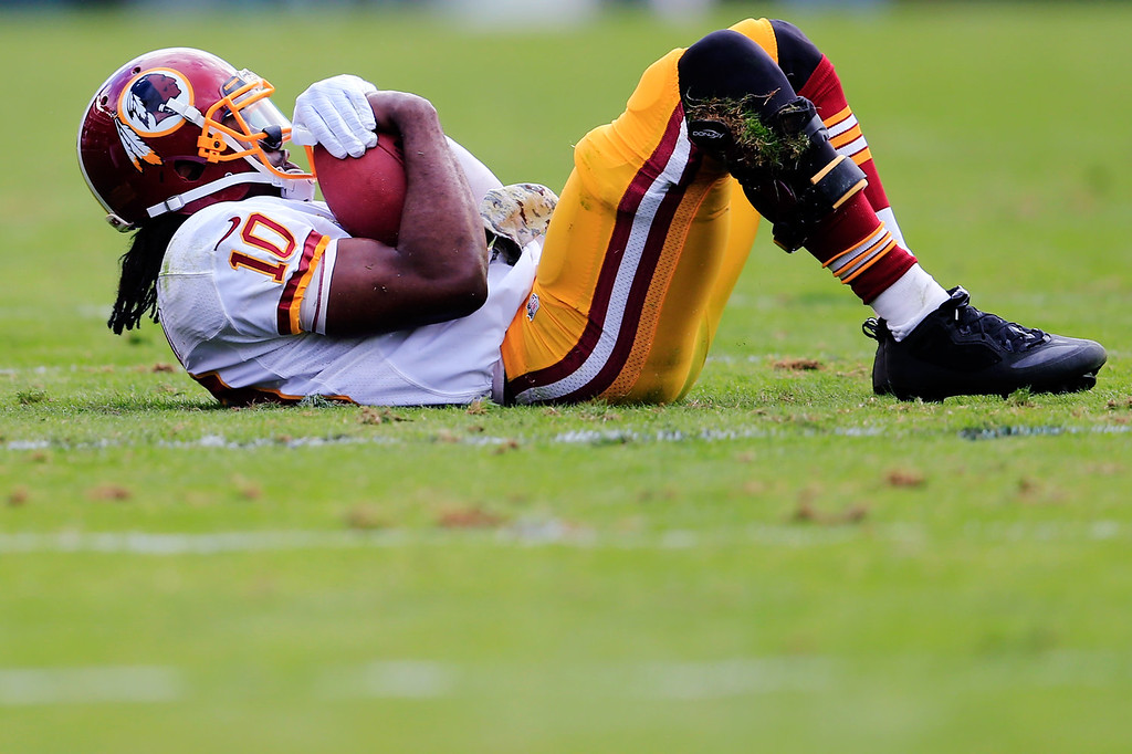 . Quarterback Robert Griffin III #10 of the Washington Redskins holds onto the ball after being tackled rushing for a gain against the Philadelphia Eagles during the first half at Lincoln Financial Field on November 17, 2013 in Philadelphia, Pennsylvania.  (Photo by Rob Carr/Getty Images)