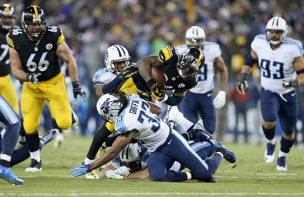 . NASHVILLE, TN - NOVEMBER 17:   Michael Griffin #33 of the Tennessee Titans tackles Le\'Veon Bell #26 of the Pittsburgh Steelers in the first quarter of the game at LP Field on November 17, 2014 in Nashville, Tennessee.  (Photo by Andy Lyons/Getty Images)