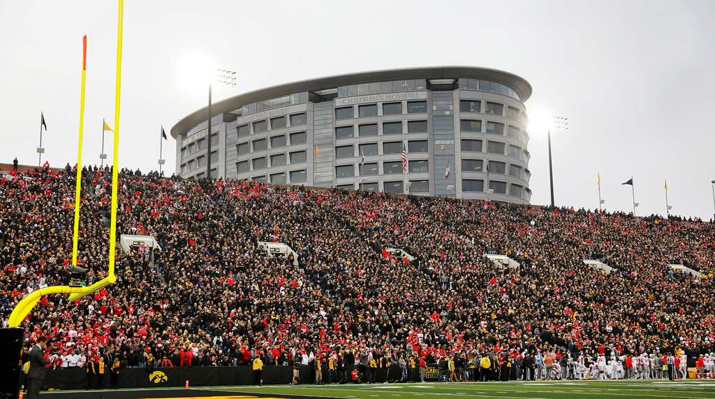 . In this Nov. 4, 2017, photo, fans watch from the University of Iowa children\'s hospital during the first half of an NCAA college football game between Iowa and Ohio State in Iowa City, Iowa. In a new tradition, known as The Wave, at the end of the first quarter fans in the 70,585-seat Kinnick Stadium turn to wave to the pediatric patients watching from the hospital, a 12-story building that overlooks the stadium from across the street. (AP Photo/Charlie Neibergall)