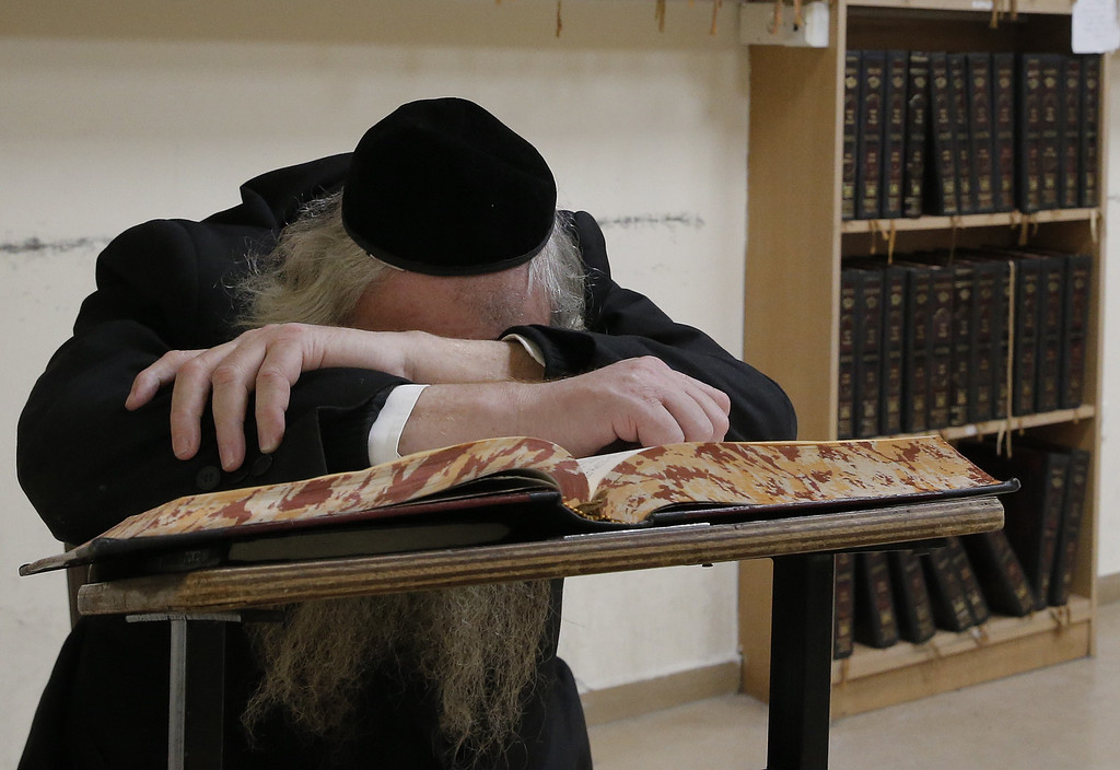 . An Ultra-orthodox Jewish man puts his head in his hands, inside a synagogue that was attacked by two Palestinians earlier in the morning in the ultra-Orthodox Har Nof neighborhood in Jerusalem on November 18, 2014. Two Palestinians armed with a gun and meat cleavers burst into a Jerusalem synagogue and killed four Israelis before being shot dead in the bloodiest attack in the city in years. AFP PHOTO/ JACK  GUEZ/AFP/Getty Images