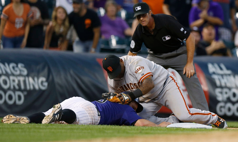 . Colorado Rockies\' Michael McKenry, left, returns safely to third base as San Francisco Giants third baseman Pablo Sandoval applies the tag under the watch of third base umpire Paul Nauert in the ninth inning of the Rockies\' 10-9 victory in a baseball game in Denver on Monday, Sept. 1, 2014. (AP Photo/David Zalubowski)