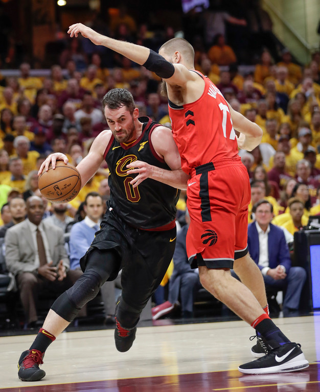 . Cleveland Cavaliers\' Kevin Love (0) drives on Toronto Raptors\' Jonas Valanciunas (17), from Lithuania, in the first half of Game 4 of an NBA basketball second-round playoff series, Monday, May 7, 2018, in Cleveland. (AP Photo/Tony Dejak)