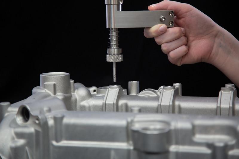 Eddy current probe testing threads in automotive cylinder head.