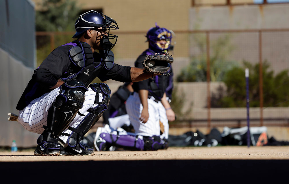 . Colorado Rockies\' Jose Gonzalez catches a pitcher during a spring training baseball workout Tuesday, Feb. 12, 2013, in Scottsdale, Ariz. (AP Photo/Darron Cummings)