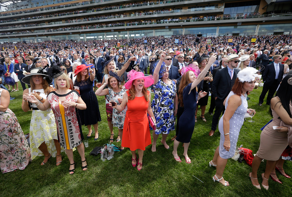 . Racegoers react as they watch a race on the second day of the Royal Ascot horse race meeting in Ascot, England, Wednesday, June 20, 2018. (AP Photo/Tim Ireland)