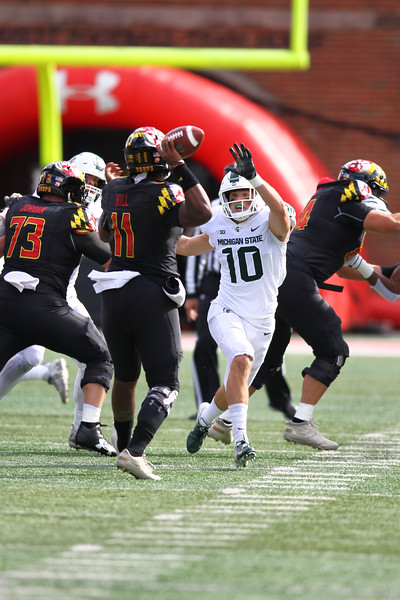 Maryland QB #11 Kasim Hill drops back to pass under pressure from Michigan State S #10 Matt Morrissey