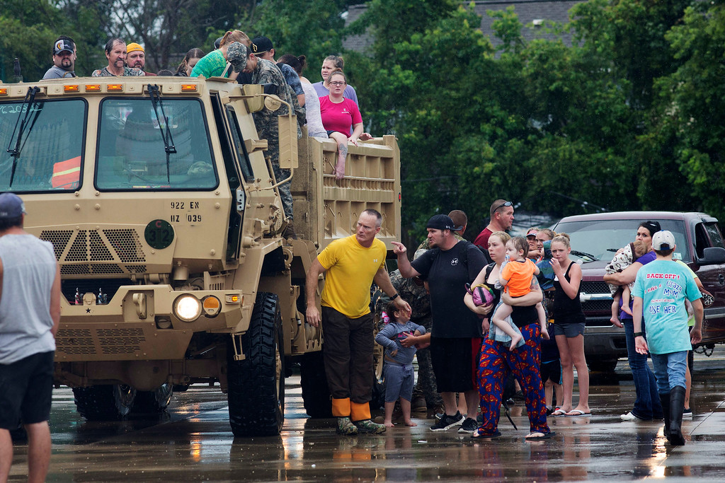 . Members of the Louisiana Army National Guard unload people at a rally point after they were rescued from rising floodwater near Walker, La., after heavy rains inundated the region, Sunday, Aug. 14, 2016. (AP Photo/Max Becherer)