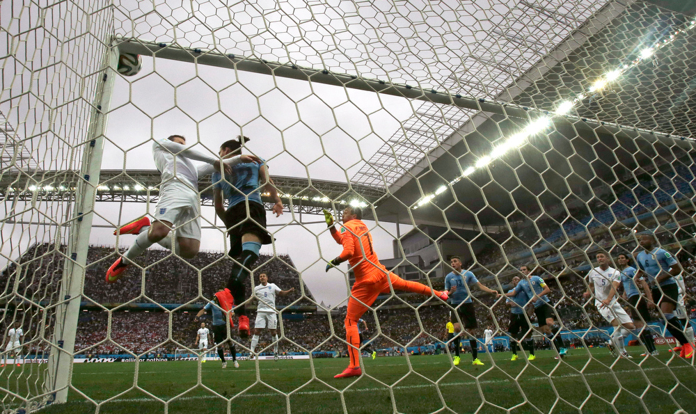 . England\'s Wayne Rooney, left, in white, heads the ball at the crossbar as Uruguay\'s goalkeeper Fernando Muslera, right in orange, watches during the group D World Cup soccer match between Uruguay and England at the Itaquerao Stadium in Sao Paulo, Brazil, Thursday, June 19, 2014.  (AP Photo/Thanassis Stavrakis)