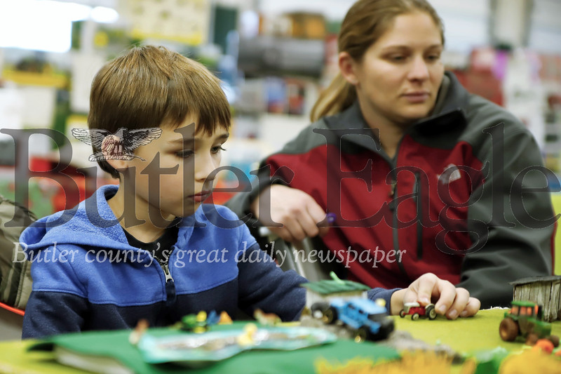 Conner Felsing, 7, of Buter plays with a tractor on his model farm at the Butler Fire Department Toy Farm Show Saturday. Seb Foltz/Butler Eagle