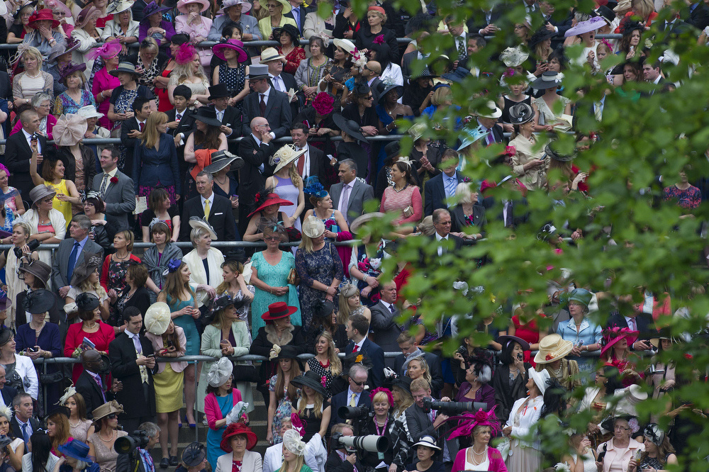 . Racegoers wait for members of the royal family to arrive on the third day of Royal Ascot, in Berkshire, west of London, on June 20, 2013. The five-day meeting is one of the highlights of the horse racing calendar. Horse racing has been held at the famous Berkshire course since 1711 and tradition is a hallmark of the meeting. Top hats and tails remain compulsory in parts of the course while a daily procession of horse-drawn carriages brings the Queen to the course.   CARL COURT/AFP/Getty Images