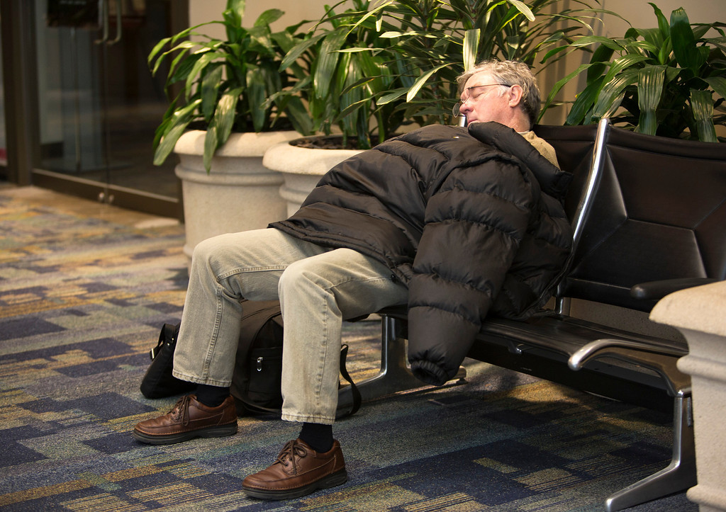 . Mike Picchietti, of Florida, takes a nap at Norfolk International Airport after learning that his flight had been canceled Wednesday, Jan. 29, 2014 in Norfolk, Va. Most flights in and out of the airport were delayed or canceled. The coast of Virginia was blanketed in up to 10 inches of snow Wednesday, with many workers in the heavily populated Hampton Roads region being told to stay home rather than travel to work in dangerous conditions. (AP Photo/The Virginian-Pilot, The\' N. Pham)