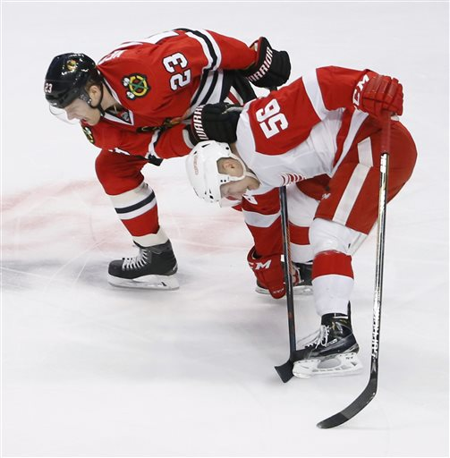 . Chicago Blackhawks right wing Kris Versteeg (23) and Detroit Red Wings left wing Teemu Pulkkinen get tangled up during the first period of an NHL hockey game Wednesday, Feb. 18, 2015, in Chicago. (AP Photo/Charles Rex Arbogast)