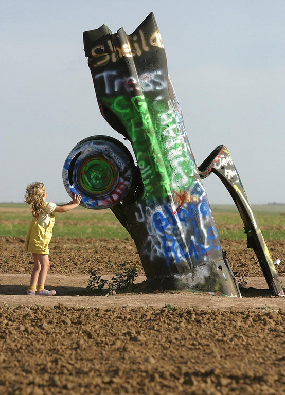 ". Four-year-old Sarah Mercer of Amarillo, Texas visits ""Cadillac Ranch\"" on historic Route 66 in Amarillo, 06 July 2003. As a tribute to America\'s relationship with one of it\'s favorite automobiles, a collective of artists called Ant Farm in 1974 placed 10 Cadillacs, ranging from a 1949 Club Coupe to a 1963 Sedan, in a wheat field located west of Amarillo.  Cadillac Ranch is a popular stopping off point for tourists on historic Route 66 which stretches from Chicago to Los Angeles.  (AFP PHOTO / Robyn BECK)"