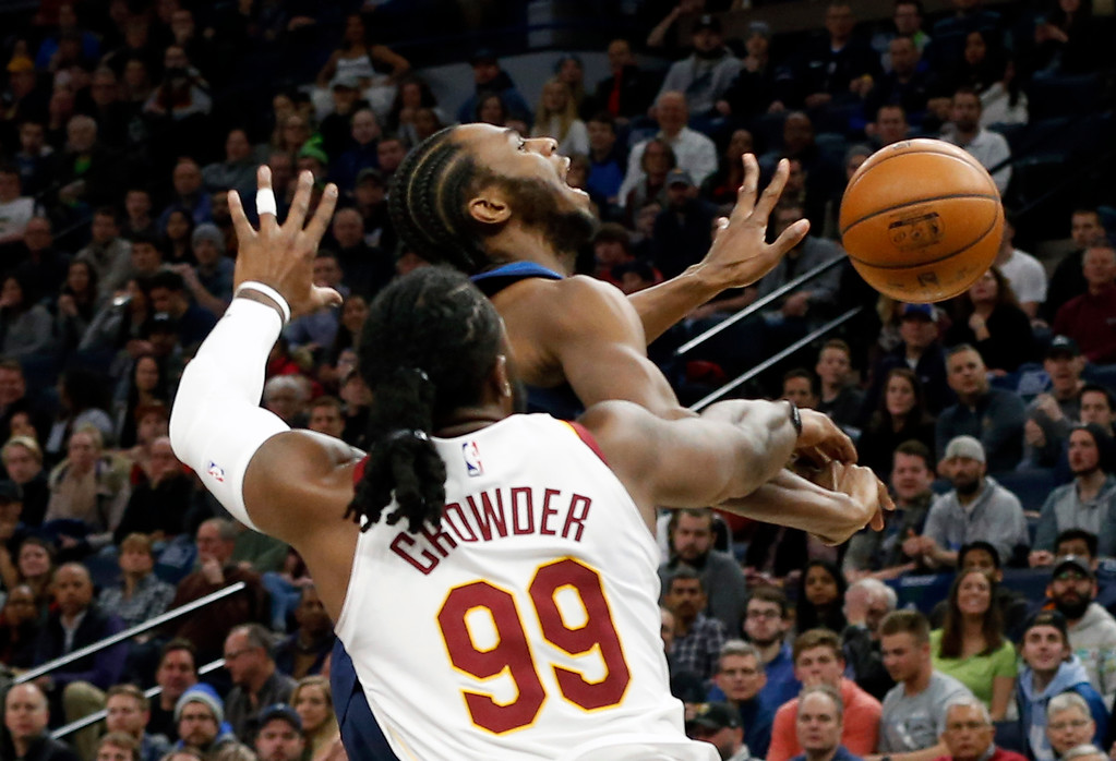 . Minnesota Timberwolves\' Andrew Wiggins, top, reacts as he is fouled by Cleveland Cavaliers\' Jae Crowder (99) in the first half of an NBA basketball game Monday, Jan. 8, 2018, in Minneapolis. (AP Photo/Jim Mone)