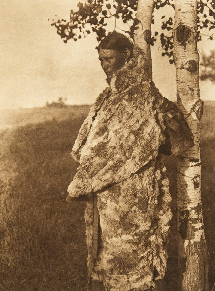 Cree woman with fur robe (The North American Indian, v. XVIII. Norwood, MA, The Plimpton Press,  1928)