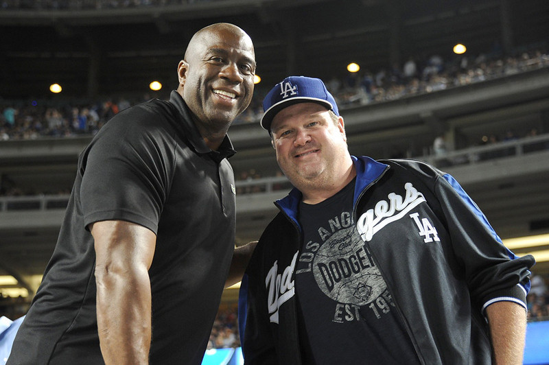. In this handout photo provided by the Los Angeles Dodgers, Magic Johnson and Eric Stonestreet attend the Cincinnatti Reds versus Los Angeles Dodgers game at Dodger Stadium on July 26, 2013 in Los Angeles, California.  (Photo by Jon Soohoo/Los Angeles Dodgers via Getty Images)