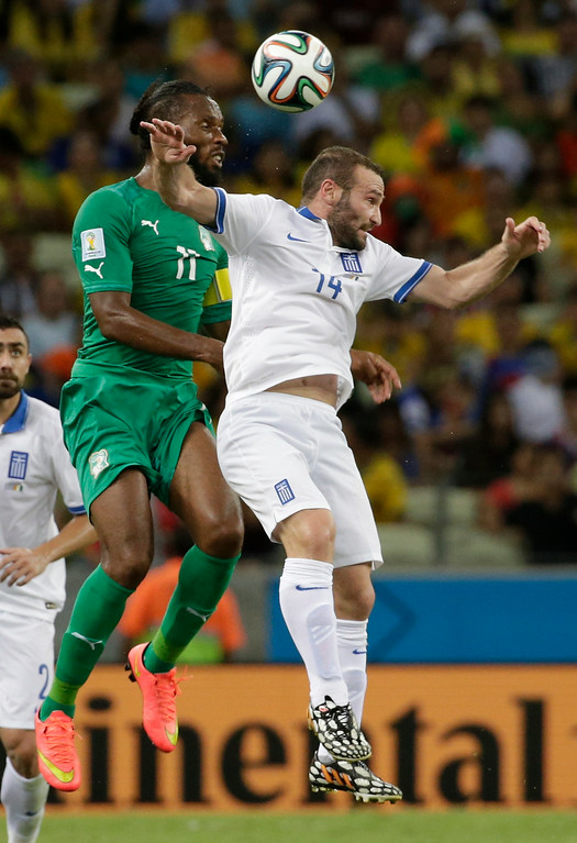 . Ivory Coast\'s Didier Drogba, left, goes for a header with Greece\'s Dimitris Salpingidis during the group C World Cup soccer match between Greece and Ivory Coast at the Arena Castelao in Fortaleza, Brazil, Tuesday, June 24, 2014. (AP Photo/Fernando Llano)