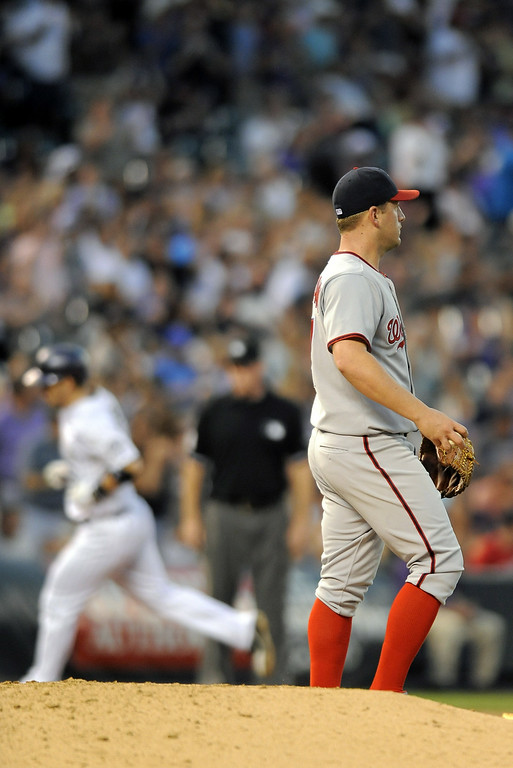 . Washington Nationals starting pitcher Jordan Zimmermann looks at right field as Colorado Rockies Corey Dickerson rounds the bases after hitting a solo home run in the sixth inning of a baseball game on Tuesday, July 22, 2014, in Denver. (AP Photo/Chris Schneider)
