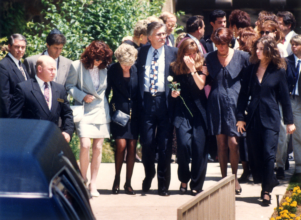. Relatives and friends of Ronald Goldman, who was murdered with O.J. Simpson\'s ex-wife, Nicole Brown Simpson, walk to his grave site.  In center, is stepmother Patti, father Fred and sister Kim (holding white rose)  (6/16/94)   (Los Angeles Daily News file photo)