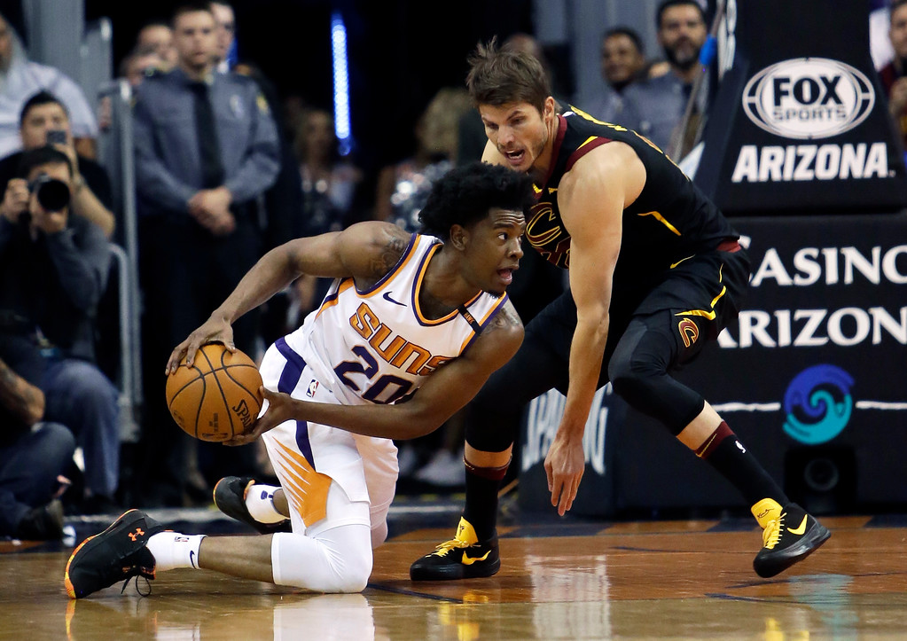 . Phoenix Suns guard Josh Jackson (20) and Cleveland Cavaliers guard Kyle Korver battle for a loose ball in the first half of an NBA basketball game, Tuesday, March 13, 2018, in Phoenix. (AP Photo/Rick Scuteri)