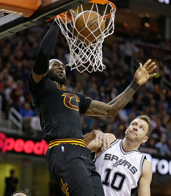 . Cleveland Cavaliers\' LeBron James, left, dunks against San Antonio Spurs\' David Lee during the second half of an NBA basketball game, Saturday, Jan. 21, 2017, in Cleveland. The Spurs won 118-115 in overtime. (AP Photo/Tony Dejak)
