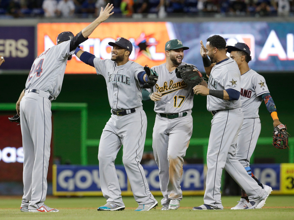 . American League\'s Seattle Mariners Robinson Cano (22), second from left, congratulated Cleveland Indians pitcher Andrew Miller, after winning the MLB baseball All-Star Game, Tuesday, July 11, 2017, in Miami. Cano hit a home run in the tenth inning to win the game. The American League defeated the National league 2-1. (AP Photo/Lynne Sladky)