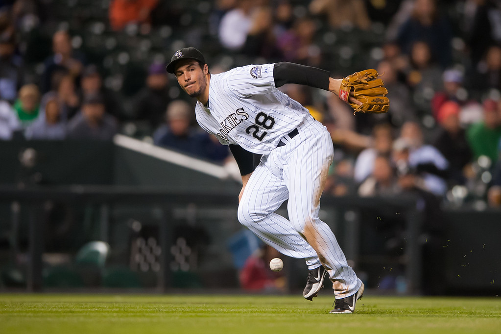 . DENVER, CO - SEPTEMBER 05:  Nolan Arenado #28 of the Colorado Rockies attempts to field a bunt hit for a single by the San Diego Padres in the sixth inning of a game at Coors Field on September 5, 2014 in Denver, Colorado.  (Photo by Dustin Bradford/Getty Images)