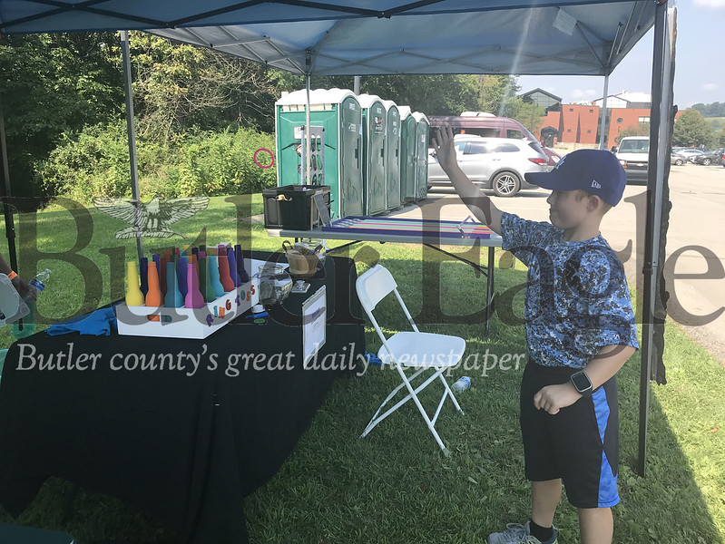 Grady Knauf, 8, plays a ring-toss game at Western Pa.'s Ride for Kids event Sunday at Seneca Valley High School to show his support for a baseball teammate who survived cancer, Keegan Dowd.