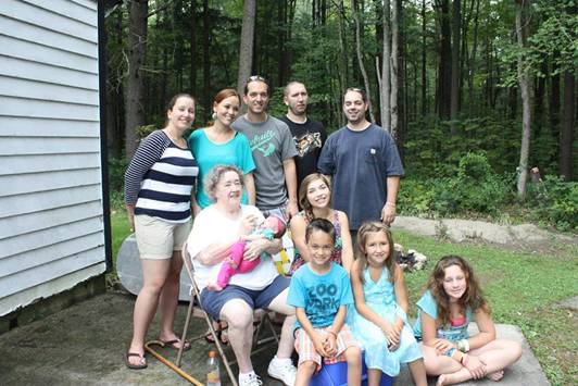 Description of . Alma Panetti with her five grandchildren and four great grandchildren in this picture.  Top row, left to right: Sarah, Lisa (Jason's Wife, Mia's Mom), Jason, Steve, Dale. Middle sitting: Alma holding Mia, Alexa. Front sitting: Mathias, Chrystina, Lexi. Sarah M. Schultz writes in an email,
