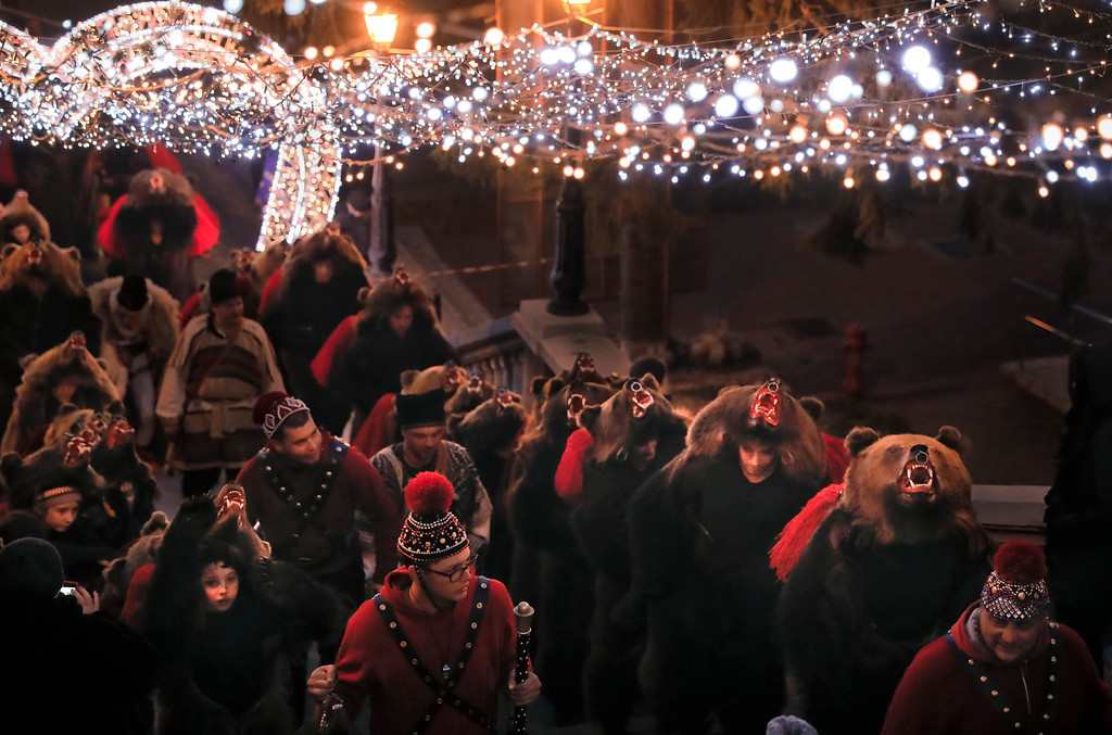 . In this Thursday, Dec. 28, 2017, picture people wearing a bear fur costumes walk under Christmas decorations in Piatra Neamt, Romania. The tradition, originating in pre-Christian times, when dancers, wearing colored costumes or animal furs, went from house to house in villages singing and dancing to ward off evil, has moved to Romania\'s cities, where the ritual is performed for money. (AP Photo/Vadim Ghirda)