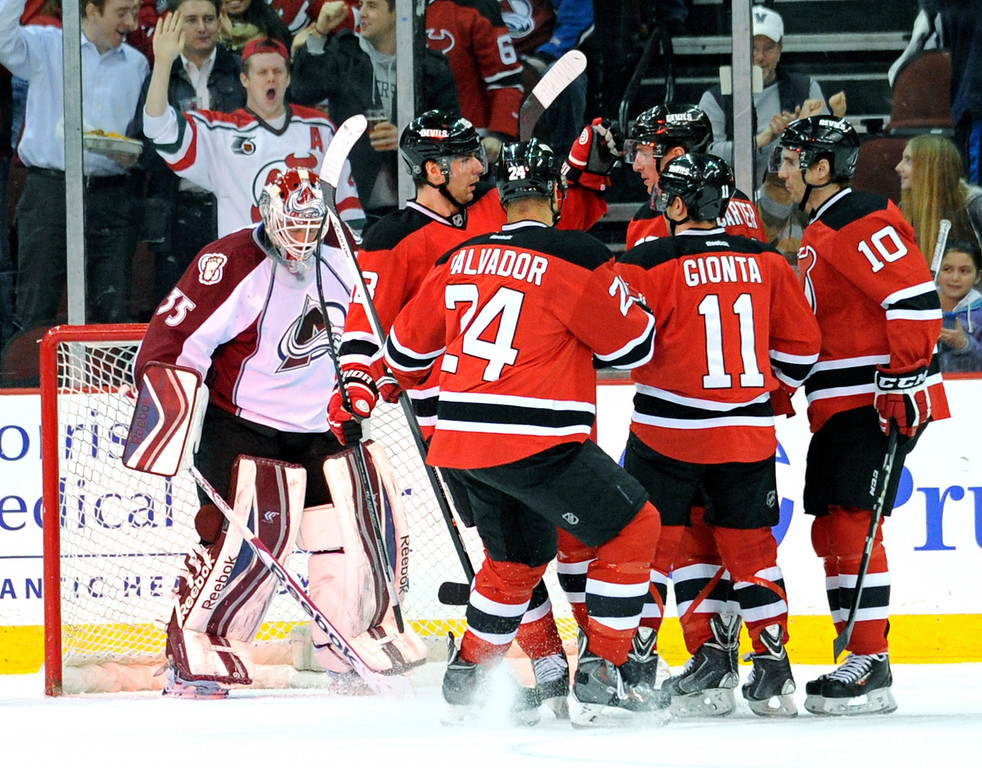 . The New Jersey Devils\' Steve Bernier (18), Bryce Salvadore (24), Brian Gionta (11) and Peter Harrold (10) and Ryan Carter celebrate Carter\'s goal as Colorado Avalanche goaltender Jean-Sebastien Giguere, left, reacts during the first period of an NHL hockey game, Monday, Feb. 3, 2014, in Newark, N.J. (AP Photo/Bill Kostroun)
