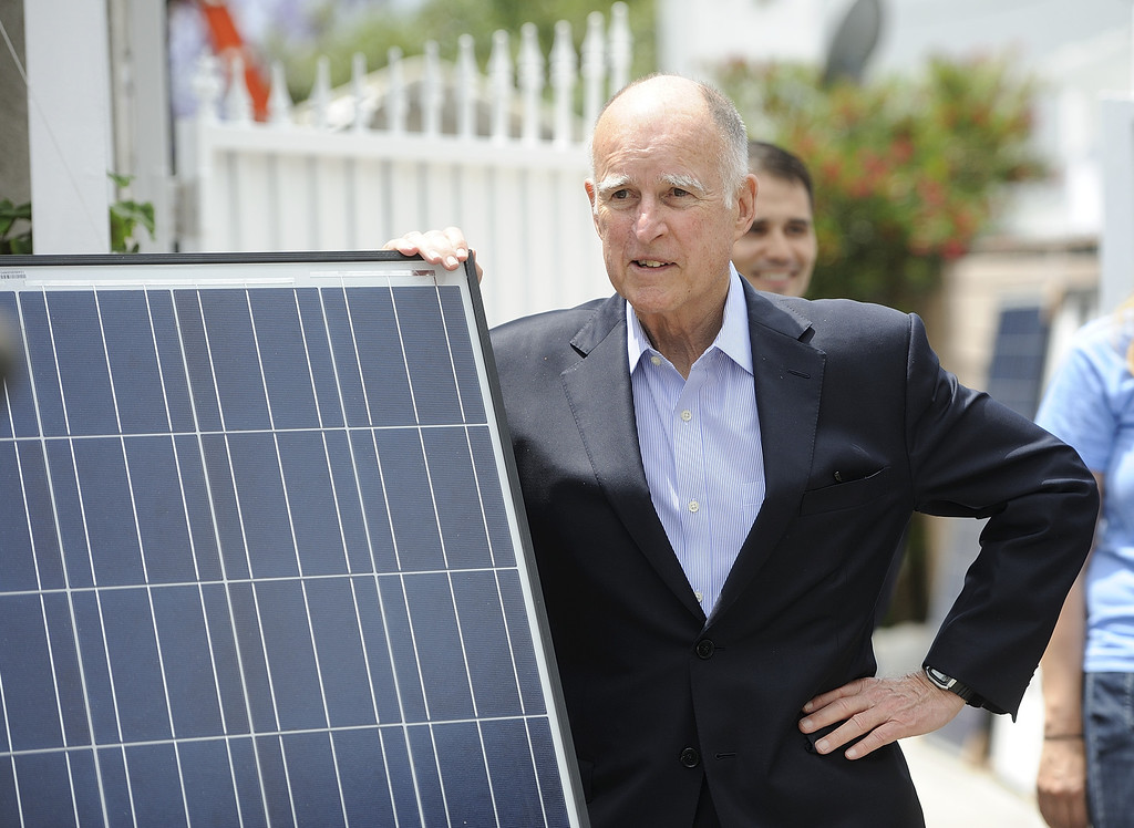 . LONG BEACH, CALIF. USA -- Gov. Jerry Brown leans on a solar panel before speaking at a north Long Beach (Calif.) home during a solar installation on Friday, May 17, 2013. This is the sixth family on this North Long Beach block to be assisted by the Single-family Affordable Solar Homes Program. This installation will allow the homeowners to save up to 90% on their electricity bills. Photo by Jeff Gritchen / Los Angeles Newspaper Group